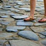 Met blote voeten op sandalen op een stenen pad